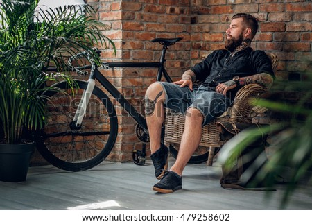 Bearded tattooed male sitting in a chair in a room with walls from red brick.