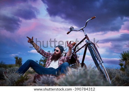 bearded traveler with suitcase and bike in the desert shouting with arms up - stock photo