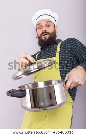 Bearded young chef  looking into the pot with an expression of disgust over gray - stock photo