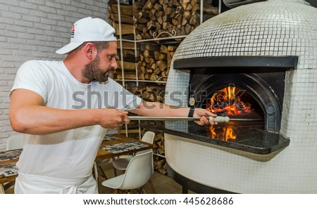 bearded young man check on pizza in wood fired oven