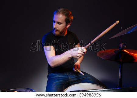 Bearded young man drummer with closed eyes sitting and playing drums over dark background - stock photo