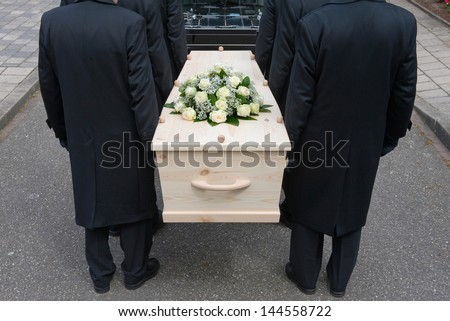 Bearers a carrying a coffin into a car - stock photo