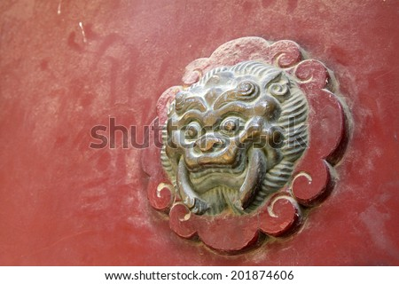 beast sculpture on red wooden door in a temple, closeup of photo