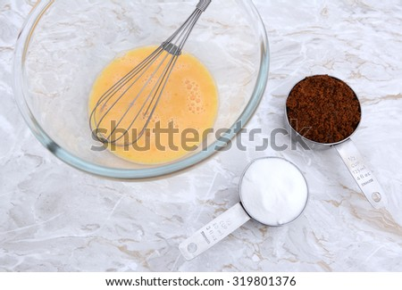 Beaten egg with balloon whisk in a bowl, measuring cups with white caster and dark muscovado sugar - stock photo