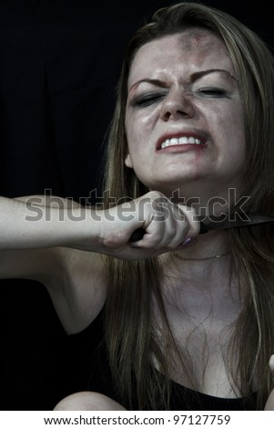Beaten white woman holding a knife to her throat with a black background - stock photo