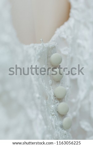 Beatiful and delicate white lace fabric detail and buttons from a bridal wedding gown.