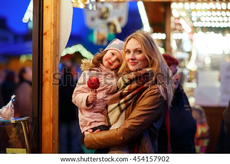 Beatiful mother and little daughter eating crystalized sugared apple on German Christmas market. Happy family in winter clothes with lights on background. Family, tradition, holiday concept - stock photo