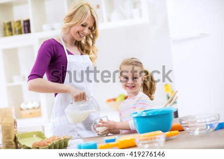 Beatiful mother pouring milk to child for breakfast