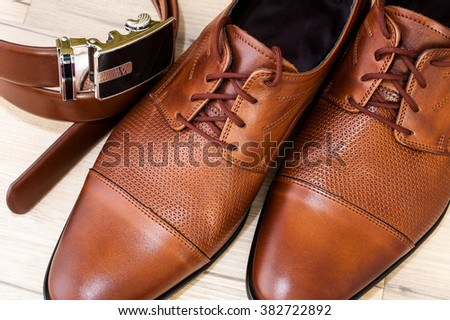 Beatiful pair of luxurious men's leather shoes accompanied by a leather belt. - stock photo