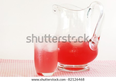 Beating the heat with an ice cold pitcher of pink lemonade on pink gingham place mat against neutral background. - stock photo