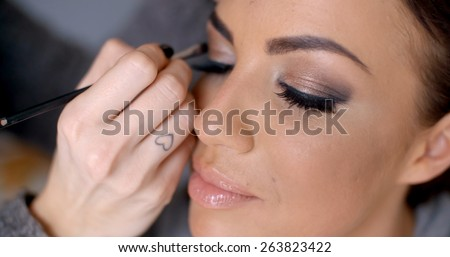 Beautician apply makeup to a glamour model darkening and enhancing the edges of her eyelids - stock photo