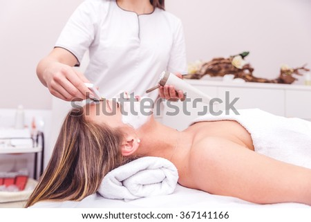 Beautician applying a beauty face mask to a woman lying down - Beauty skin treatment in a spa resort centre - stock photo