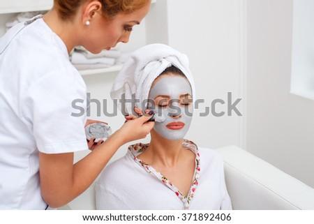 Beautician Applying Mask On Customer's Face At Salon - stock photo