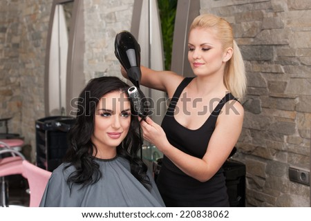 Beautician blow drying woman's hair after giving new haircut at parlor. blond girl drying dark-haired girl hair and smiling - stock photo