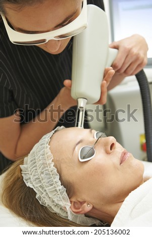 Beautician Carrying Out Fractional Laser Treatment - stock photo