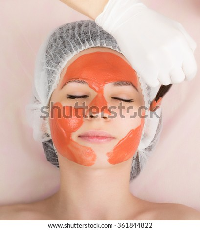 beautician does cosmetic mask on the patient's face, professional consultation.  - stock photo