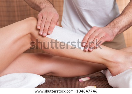Beautician doing depilation for young woman at spa salon