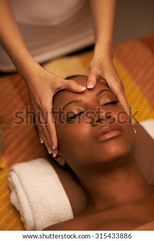 Beautician doing facial massage  to her  beautiful female client - stock photo