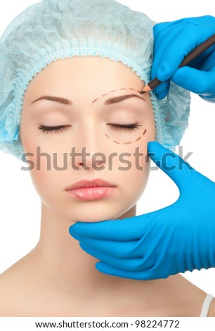 Beautician drawing perforation lines on woman face before plastic surgery operation - stock photo