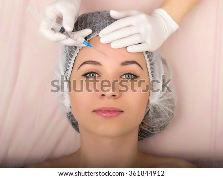 Beautician examining the face of a young female client at spa salon. beautician beauty injections. Professional consultation.