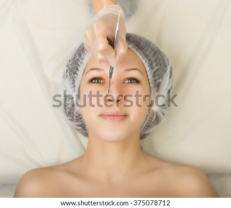 Beautician examining the face of a young female client at spa salon. face cleaning, Una cuchara. Professional consultation - stock photo