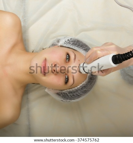 Beautician examining the face of a young female client at spa salon. getting rf-lifting in a beauty salon. Professional consultation. - stock photo