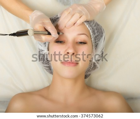 Beautician examining the face of a young female client at spa salon. Permanent makeup, tattoo in a beauty salon. Professional consultation. - stock photo