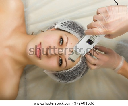 Beautician examining the face of a young female client at spa salon. ultrasonic cleaning person. Professional consultation - stock photo