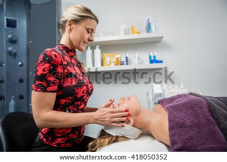 Beautician Giving Facial Massage To Woman In Beauty Parlor - stock photo