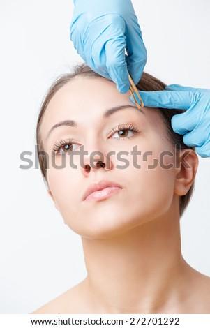 beautician in disposable gloves plucks eyebrows with tweezers brunette - stock photo