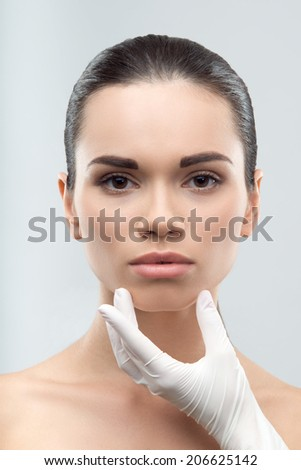 Beautician in white rubber gloves touching face of young beautiful woman. Plastic surgery. Close up portrait isolated on grey background - stock photo