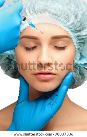 Beautician makes a cosmetic injection to woman face, in forehead. Isolated on white background - stock photo