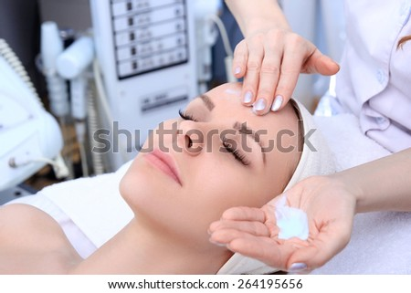Beautician makes cleansing and exfoliating facial for beautiful girl. Beauty salon. - stock photo