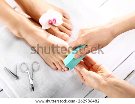 Beautician polishing nails, pedicure. Foot care treatment and nail, the woman at the beautician for pedicure. - stock photo