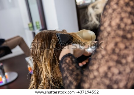 Beautician Styling Client's Hair In Salon - stock photo