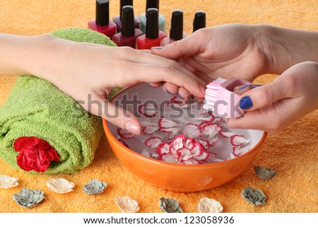 Beautician taking care of hands, beauty salon - stock photo
