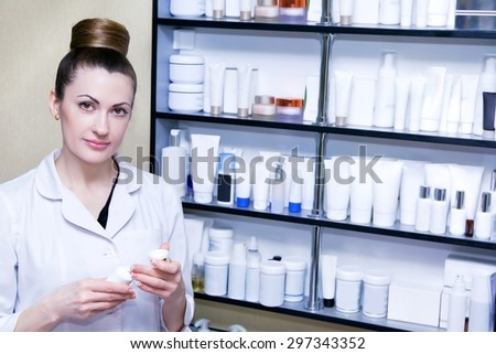 Beautician with container cream in hand in his office cosmetology