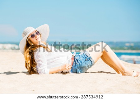 Beautifil young caucasian woman lying on the beach in white hat at sunny day enjoing summer vacation