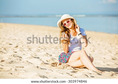 Beautifil young caucasian woman on the beach in white hat taking selfie picture with mobile phone. Sunny day on summer vacation - stock photo