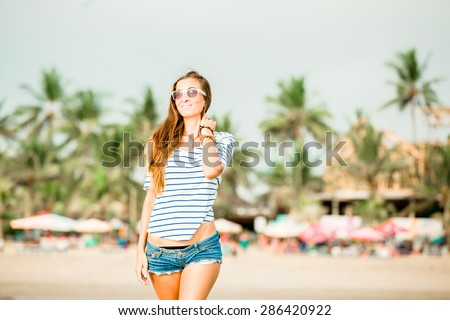 Beautifil young woman with long legs walking along the beach at sunset with palms at the background - stock photo