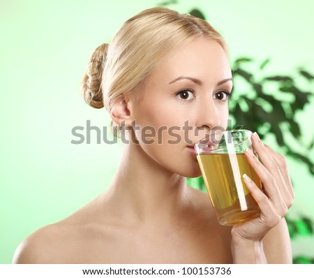 Beautifu and youngl blonde with cup of green hot tea - stock photo