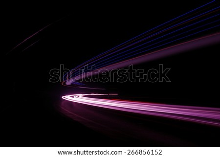 Beautiful abstract car lights trails in a car tunnel in white, green, purple,red - stock photo