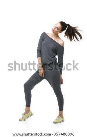 Beautiful active young woman in grey overalls. Isolated over white background. Copy space.