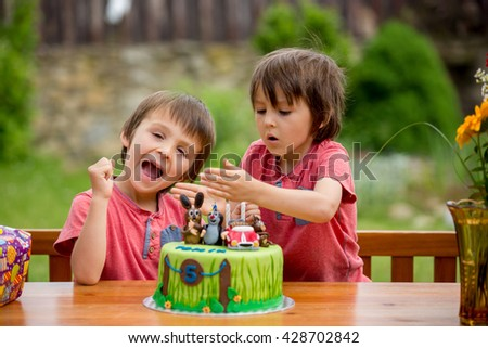 Beautiful adorable five year old boy, celebrating his birthday, blowing candles and eating the cake, outdoors. Birthday party for kids - stock photo