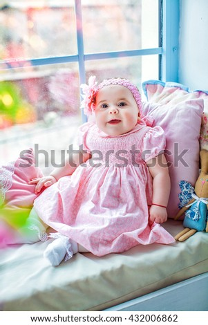 Beautiful adorable little baby girl in pink dress with bow, sitting at the window. Happy childhood of the child. Closeup, macro. - stock photo