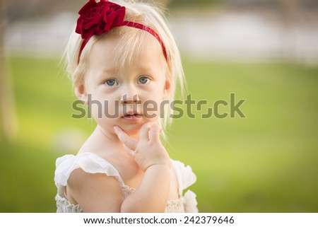 Beautiful Adorable Little Girl With Her Hand On Her Face Wearing White Dress In A Grass Field. - stock photo