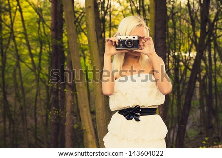 Beautiful adult girl with retro photo camera in a forest - stock photo