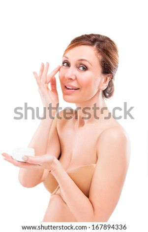 beautiful adult woman applying cream on face.