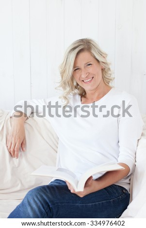 beautiful adult woman with blonde hair sitting at home on the sofa with a book / album in hand. Reading, smiles for the camera