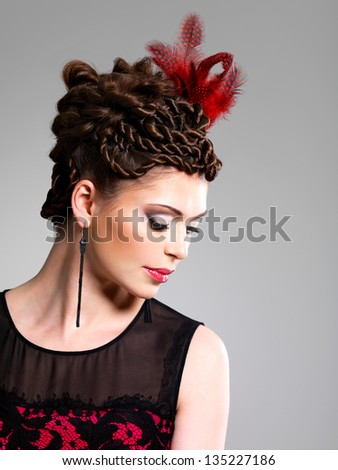 Beautiful adult woman with fashion hairstyle with red feather in hairs